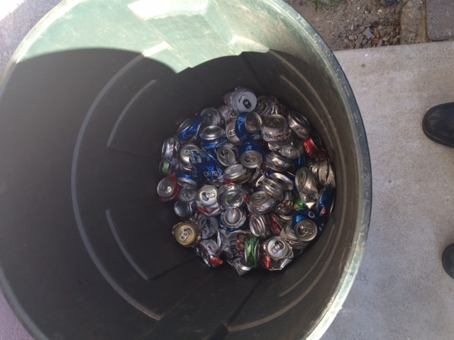 A garbage can full of soda cans after crushing